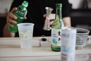 A person is pouring a drink while bottles of Soju and cups sit on the table